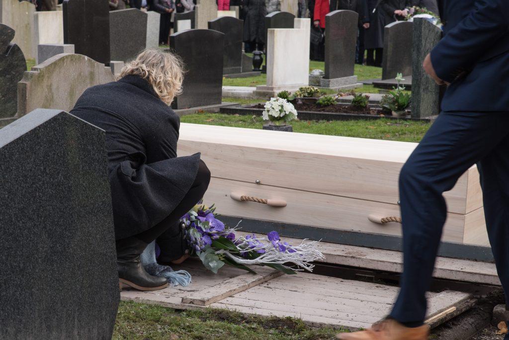 rouwbloemen en een kist bij het graf