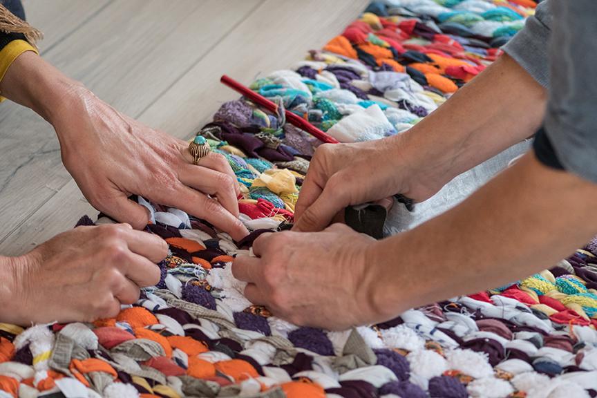 Vier handen werken aan het weven van een kleurrijke afscheidswade. Een close-up foto van deze handeling door Kritsel Dallinga afscheidsfotograaf.